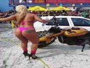 Mulher sendo paga para lavar os carros de bikini